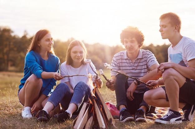 Il colpo orizzontale dei migliori compagni femminili e maschili felici frigge i marshmallow, si siede vicino al fuoco, gode della giornata di sole, ha buoni rapporti, discute il piano futuro dopo la laurea all'università. concetto di pic-nic