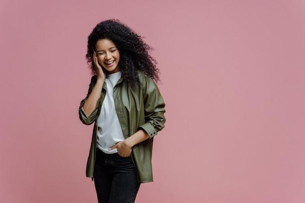 Il colpo orizzontale della donna afroamericana felice tiene la mano in tasca