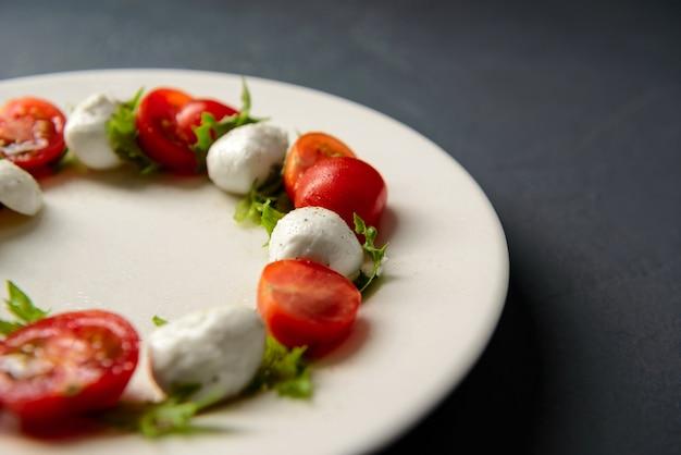 Il colpo potato del primo piano del piatto con insalata caprese è servito in ristorante
