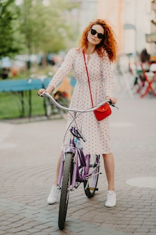 Il colpo verticale della donna dai capelli rossi riccia cavalca la bicicletta in città durante la settimana, ha tempo libero