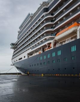Il colpo verticale di angolo basso di una nave da crociera enorme ha attraccato in islanda sotto il chiaro cielo