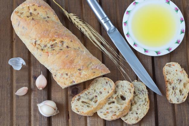 Il coltello da pane, olio vegetale, aglio e ramoscello d'orzo. vista dall'alto