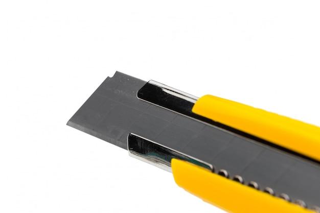Il coltello giallo della cancelleria isolato su bianco
