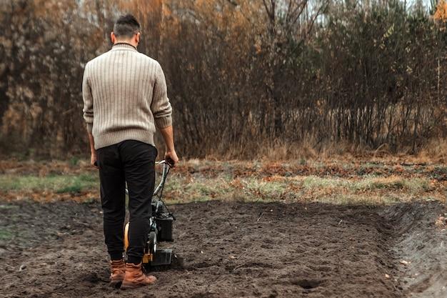 Il coltivatore allenta il terreno.