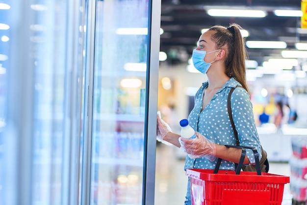Il compratore casuale della giovane donna in una mascherina protettiva medica con il cestino della spesa sceglie i prodotti lattier-caseario dal congelatore in una drogheria