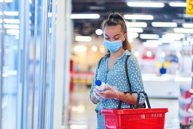 Il compratore della giovane donna in una maschera protettiva medica e guanti con il cestino della spesa sceglie i prodotti lattier-caseario dal congelatore in un centro commerciale