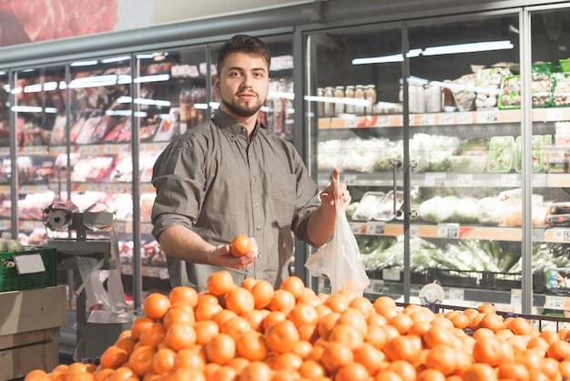 Il compratore sorridente compra la frutta in un supermercato.
