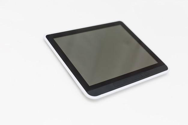 Il computer della compressa con il modello dello schermo in bianco si trova sulla superficie, isolata su fondo bianco.