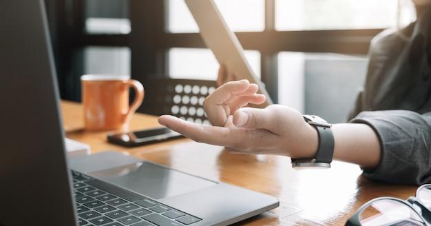 Il computer della compressa di uso della giovane donna per l'affare analizza e passa la mano sul computer
