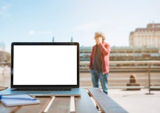 Il computer portatile; blocco note e penna sul tavolo in legno con uomo in piedi in fondo