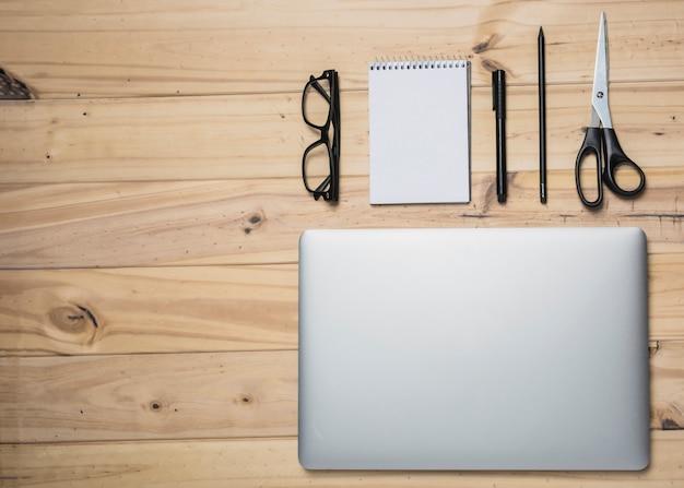 Il computer portatile; cartolerie e occhiali sulla superficie in legno