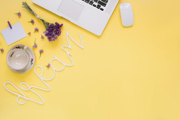 Il computer portatile; fiori viola con la parola da sogno e tazza vuota su sfondo giallo