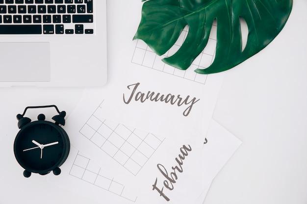 Il computer portatile; foglia di formaggio svizzero; sveglia nera; parola scritta gennaio e febbraio testo su un foglio bianco su scrivania bianca