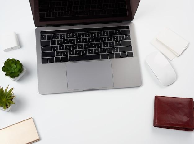 Il computer portatile grigio aperto si leva in piedi su una tabella bianca, vicino ad un mouse senza fili, il posto di lavoro delle free lance, l'uomo d'affari, vista superiore