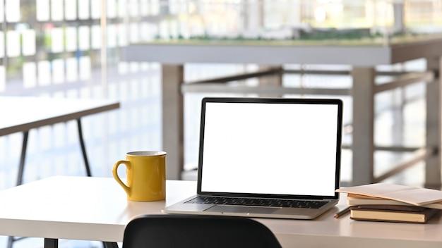 Il computer portatile moderno con la visualizzazione in bianco in bianco e le attrezzature per ufficio stanno mettendo sulla scrivania bianca sopra l'ufficio moderno