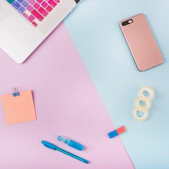 Il computer portatile; smartphone; nastro per violoncello e nota adesiva su carte di cartone colorate