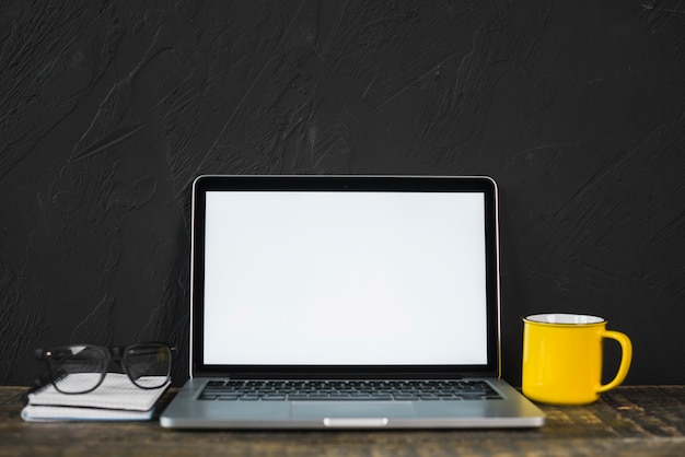 Il computer portatile; spettacolo; tazza e diario di caffè giallo sul tavolo con parete strutturata nera