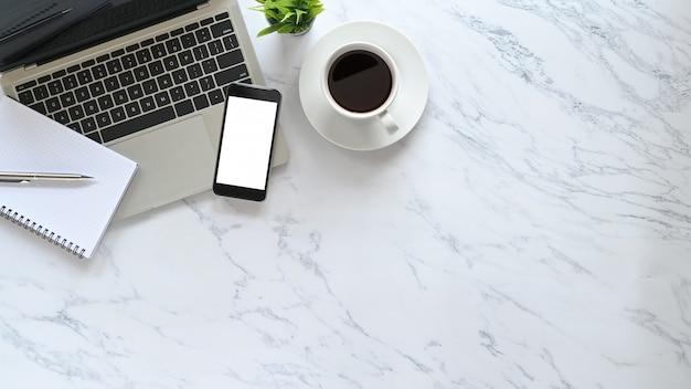 Il computer portatile stilizzato di marmo piano della scrivania, la penna, il taccuino, il caffè con la pianta ed il modello telefonano sullo spazio della copia di vista superiore.