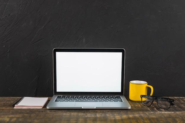 Il computer portatile; tazza; blocco note e occhiali sulla superficie in legno