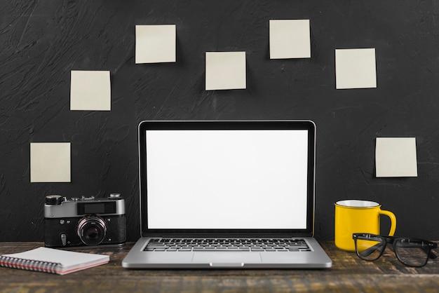 Il computer portatile; tazza; occhiali; blocco note a spirale e fotocamera davanti a note adesive stucked sulla lavagna
