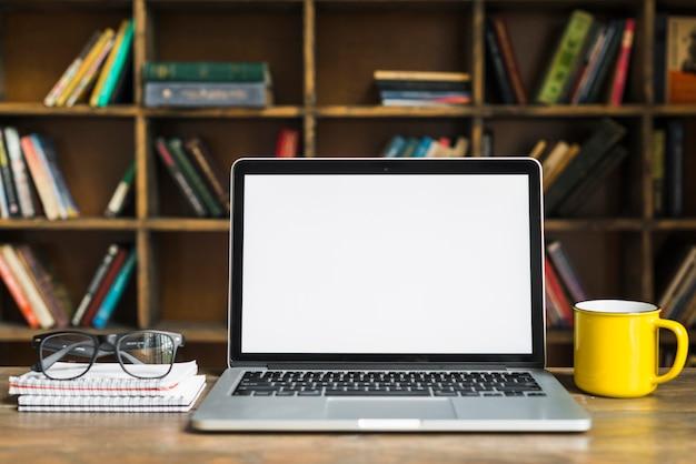 Il computer portatile; tazza; occhiali e blocco note a spirale sulla scrivania in legno