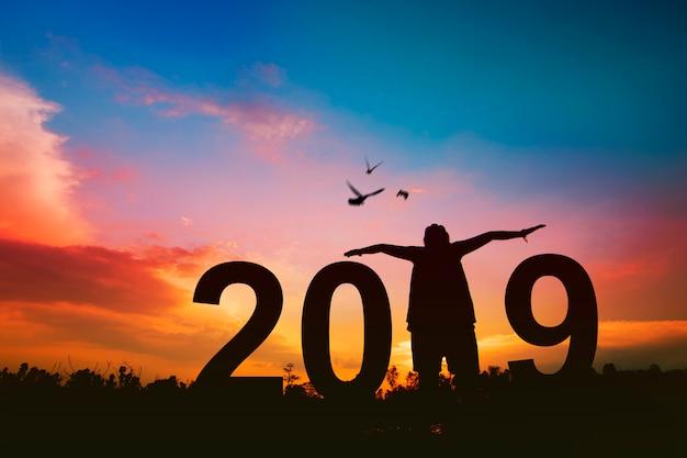 Il concetto 2019 del nuovo anno, siluetta della donna felice ha libertà e allegro con gli uccelli che volano sul cielo