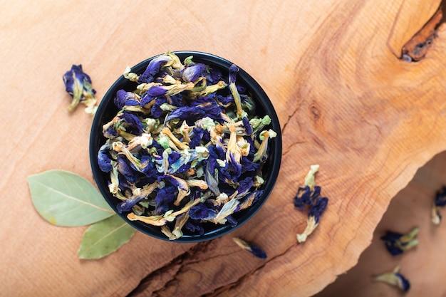 Il concetto asciutto del fiore del pisello di farfalla dell'alimento per fa la tisana in tazza di ceramica sul bordo di legno