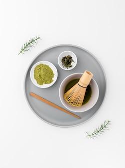 Il concetto del tè di matcha su un vassoio con bambù sbatte