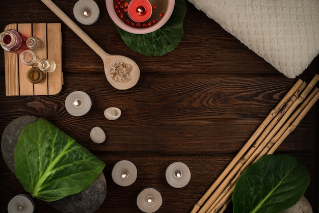 Il concetto della stazione termale, composizione accogliente con sale da bagno, cucchiaio di legno, pietre e candele sulla tavola di legno del salone della stazione termale con sano si rilassa l'atmosfera meditativa