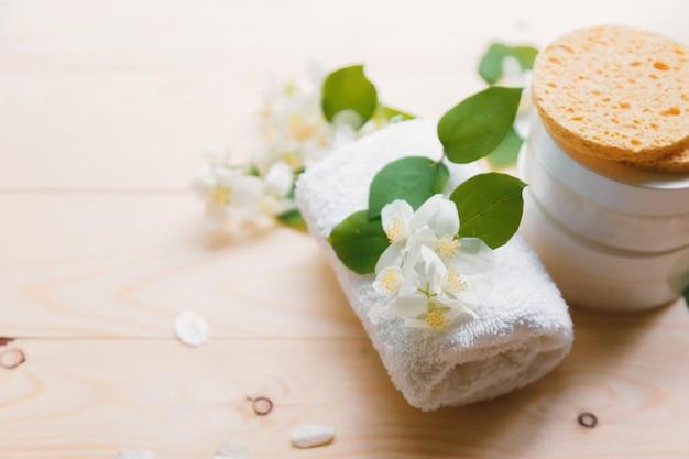 Il concetto della stazione termale dell'aroma con il gelsomino fiorisce su una tavola, su una sanità e su una stazione termale di legno bianche