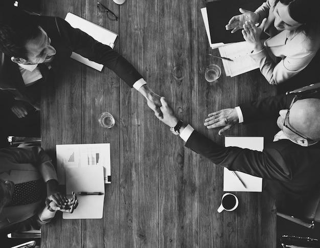 Il concetto della stretta di mano di meetng della squadra di affari applaude
