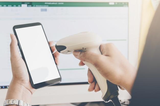 Il concetto di acquisto e le mani umane stanno tenendo lo smartphone con il lettore di codici a barre.