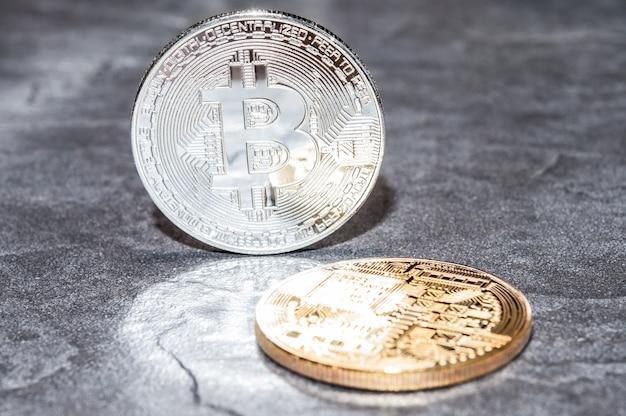 Il concetto di argento e oro bitcoin su uno sfondo di pietra.