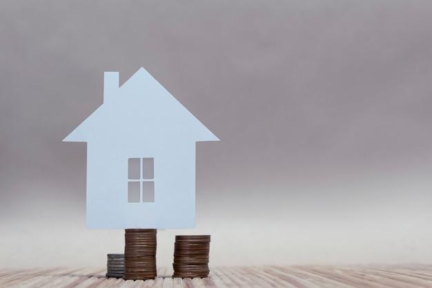 Il concetto di casa da carta su una pila di monete