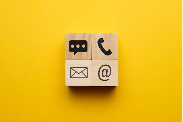 Il concetto di contatti telefonici, e-mail, messaggistica istantanea con icone su blocchi di legno.