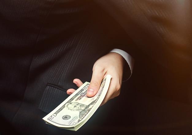 Il concetto di corruzione e tangenti, legge e denaro. affari oscuri. l'uomo d'affari riceve denaro