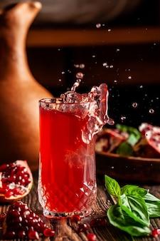 Il concetto di cucina georgiana e armena. bevanda fresca con ghiaccio di basilico e succo di melograno in un calice di vetro. immagine di sfondo. copia spazio