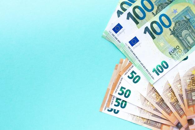 Il concetto di denaro e finanza. banconote da 100 e 50 euro disposte su uno sfondo blu sul lato destro. con posto per il testo.