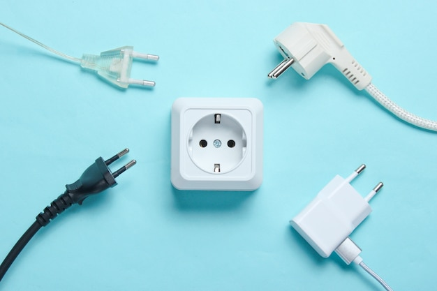 Il concetto di dipendenza elettrica. molte spine di alimentazione vicino alle prese di corrente
