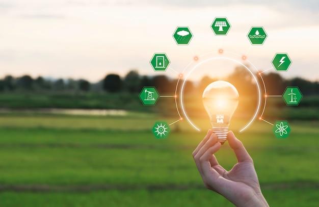 Il concetto di energia e innovazione della mano tiene una lampadina e copia lo spazio per inserire il testo.