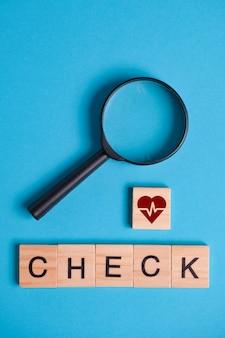 Il concetto di esame, controllo del cuore. il segno sulla piazza di legno accanto alla lente d'ingrandimento