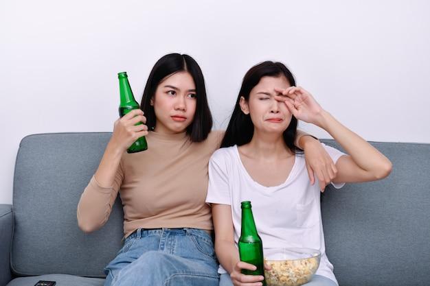 Il concetto di guardare la televisione. ragazze asiatiche che guardano la televisione con diverse sensazioni.