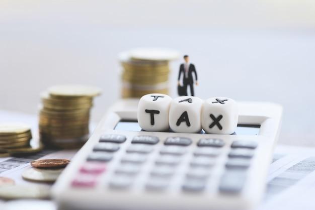 Il concetto di imposta e le monete impilate del calcolatore sulla fattura fatturano la carta per la tassa di tempo che riempie il pagamento di debito pagato