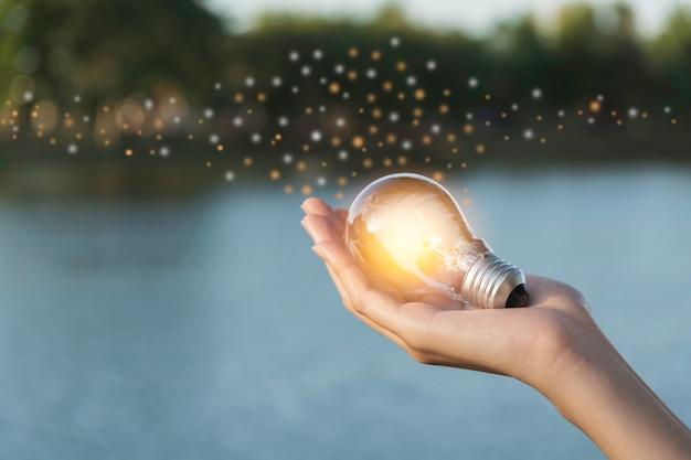 Il concetto di innovazione ed energia della mano tiene una lampadina