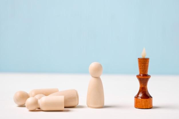 Il concetto di licenziamento dei dipendenti. la figura del re di legno su uno sfondo blu guarda le figure.