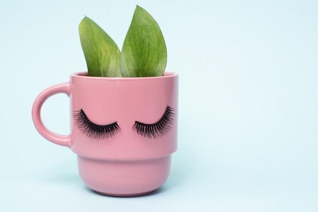 Il concetto di mattina femminile e caffè naturale. tazza rosa di caffè del mattino con orecchie come un coniglio di foglie verdi. copyspace