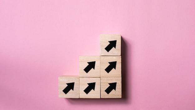 Il concetto di mentalità di processo di successo della crescita di affari, freccia firma la direzione sul cubo di legno