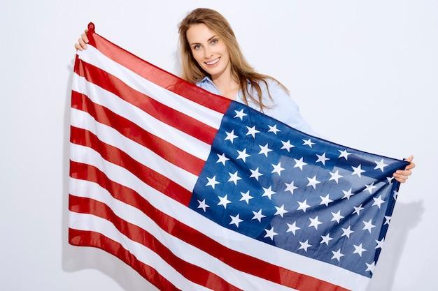 Il concetto di migrazione, festività nazionali e festività nazionali e festa dell'indipendenza del 4 luglio. donna in possesso di una bandiera americana su uno sfondo bianco e sorriso.