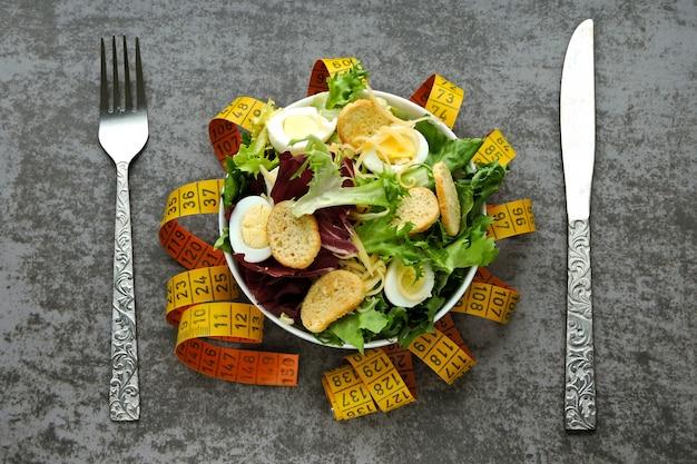 Il concetto di nutrizione dietetica. insalata sana con uova di quaglia e foglie verdi. nastro di misurazione. il concetto di perdita di peso attraverso l'alimentazione.