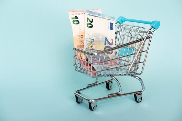 Il concetto di pianificazione finanziaria, molti nel carrello isolato sul blu